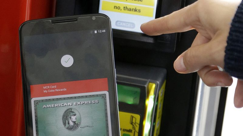A Google employee gives a demonstration of Android Pay on a phone at Google I/O 2015 in San Francisco, Thursday, May 28, 2015. Google's next version of its Android operating system will boast new ways to fetch information, pay merchants and protect privacy on mobile devices as the Internet company duels with Apple in the quest to make their technology indispensable. (AP Photo/Jeff Chiu)